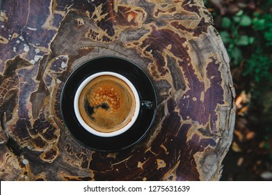 Americano coffee, a coffee mug placed on a log in the garden