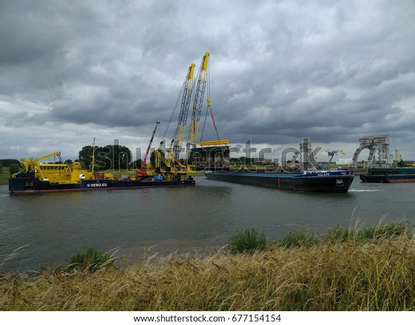AMERONGEN, THE NETHERLANDS - JUNE 2017: crane vessel loads a visor-type gate into a barge. The weir ensemble Nederrijn & Lek  requires a large-scale renovation after some 50 years of operation.