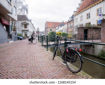 Amersfoort, netherlands, 15 december 2018: Woman on bicycle passes other bikes in narrow medieval street next to canal in city of amersfoort