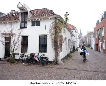 Amersfoort, Netherlands, 15 december 2018: woman on bicycle passes other bikes in narrow medieval street in city of amersfoort in hollan
