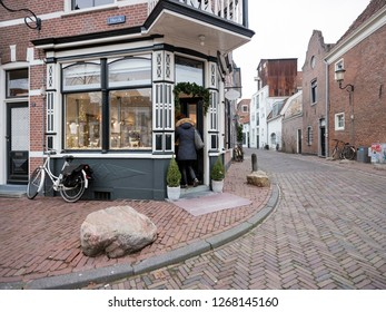 Amersfoort, Netherlands, 15 december 2018: woman enters old shop in medieval centre of amersfoort in the netherlands