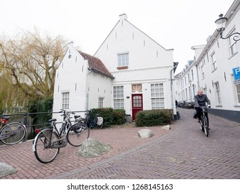 Amersfoort, Netherlands, 15 december 2018: man on bicycle passes other bikes in narrow medieval street in city of amersfoort in the netherlands