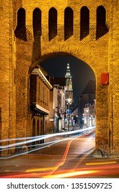 Amersfoort, Netherlands - 16 Februari2019: Old city gate with illuminated city center in the evening with driving traffic Amersfoort, Netherlands.