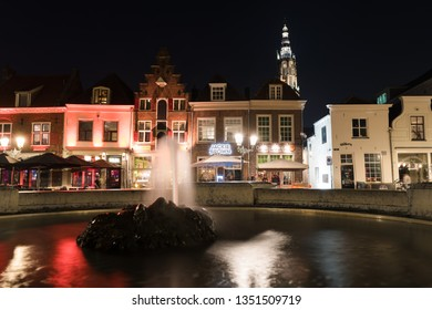 Amersfoort, Netherlands - 16 Februari2019: Water squirting fountain on old square with bars and shops in the city center of Amersfoort, Netherlands.