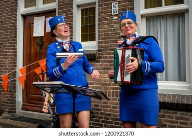 Amersfoort, the Netherlands - April 27, 2018 : Dressed at KLM stewardesses singing for people passing by, at the flee market on King's day