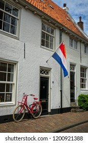Amersfoort, the Netherlands - April 27, 2018 : Bicycle parked in front of an old house in the old city of Amersfoort on King's day