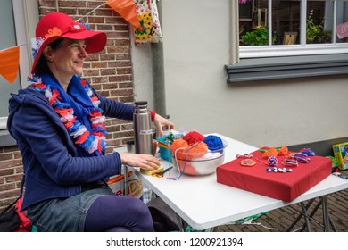 Amersfoort, the Netherlands - April 27, 2018 : Woman waiting for buyers for her handmade merchandise on King's day