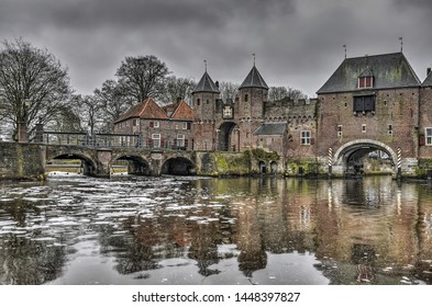 Amersfoort, The Netherlands, February 26, 2017: 14th century Koppelpoort across the river Eem and an adjacent bridge across the Beek on a grey day in winter