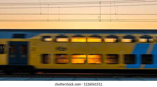Amersfoort, The Netherlands - June 28, 2018: train of the NS passing by at Amersfoort with the sunset behind the train.