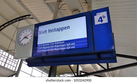 Amersfoort / Netherlands - September 25 2016: Clock and digital display informes about the next train on a dutch railway station. Text: Niet instappen (do not board)