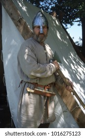 Amersham Buckinghamshire England 2002. A reenactor dresses as a Viking Warrior he wears a conical helmet and wears a scramasax knife for protection and stands in a Viking camp environment.