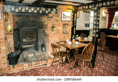 "Amersham, England - July 14, 2017: The traditional English interior of the historical pub in the hotel ""Saracens Head Inn"". The tables served for the breakfast next to the fireplace. Retro style."