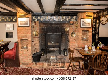 "Amersham, England - July 14, 2017: The fireplace  in the historical traditional  English pub of the hotel ""Saracens Head Inn"". Ancient building, 17th century. Vintage interior."