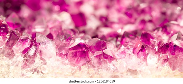 Amethyst pink crystals. Gems. Mineral crystals in the natural environment. Texture of precious and semiprecious stones. Seamless background with copy space colored shiny surface of precious stones.