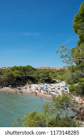 AMETLLA DE MAR, SPAIN - AUGUST 26, 2018: Vacationers at the Cala Calafato beach in Ametlla de Mar, Spain, in the popular Costa Daurada coast