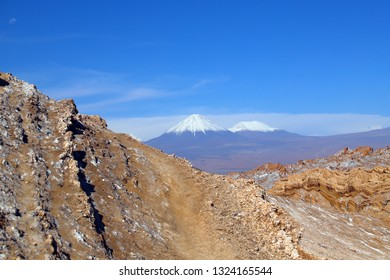 The Amfitheater in Valley of the Moon (Valley of the Moon) with the snowy Licancabur volcano in the background, the white in the foreground is salt, Atacama Desert, Chile