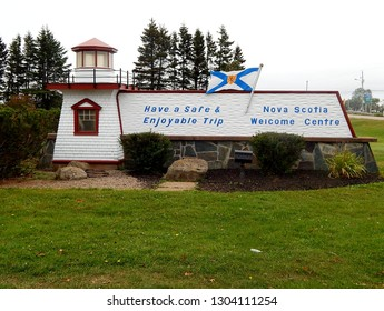 Amherst, Nova Scotia, Canada - September 18, 2017: Sign outside the Welcome Centre in Nova Scotia, Canada, with a red and white lighthouse. The flag of the Nova Scotia province is flying above.