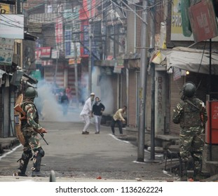 Amid tear smoke gas Kashmiri Muslim protesters hurling stones on the police forces during the clashes erupted between Indian government forces and mobs, on 16 June 2018, in Kashmir's Anantnag town.