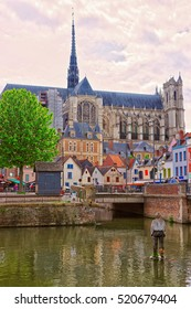 Amiens Cathedral of Notre Dame and traditional houses on La place du Don Street at the embankment of Somme canal, Picardy, France. People on the background