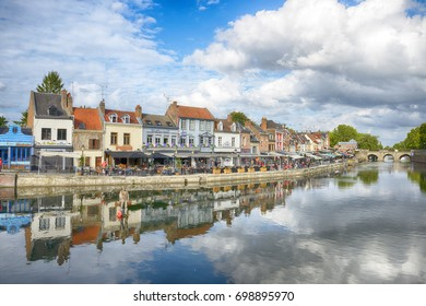 Amiens, France - JULY 27, 2017: Quay of Belu with traditional houses and Somme River in Amiens, Picardy, France. People sitting in cafes.