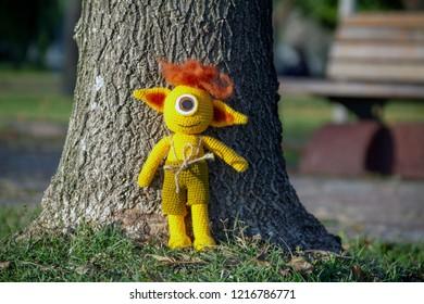 amigurumi crochet cyclops monster standing under a tree at park