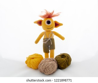 amigurumi crochet yellow cyclop monster and wool balls isolated on white