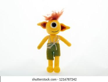 amigurumi crochet yellow cyclops monster toy isolated on white