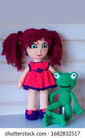 Amigurumi doll girl and green frog photographed on a white background.