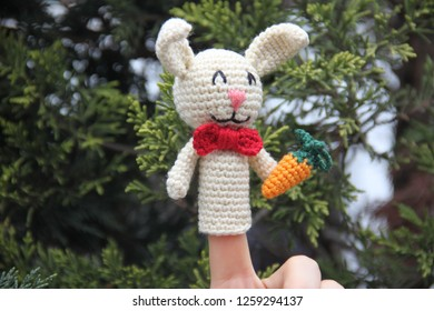 Amigurumi rabbit finger puppet that is holding knitted carrot in front of green background