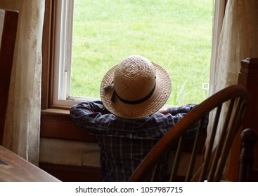 Amish Boy Looking Out House Window