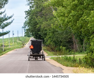 Amish buggy from behind travelling down a country road. Slow moving vehicle triangle sign on black carriage.