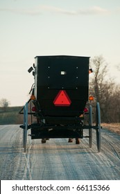 Amish buggy with a horse riding on gravel rural road