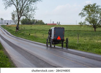 Amish buggy traveling up a road in rural Lancaster County Pennsylvania.