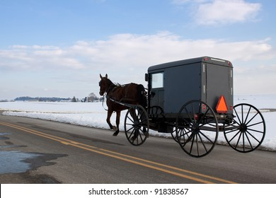An Amish Carriage travels in snow covered Lancaster County,Pennsylvania,USA.