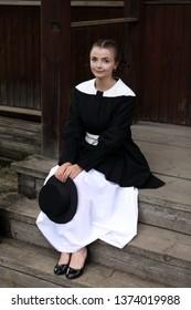 Amish fashion style. Fashion girl wearing stylish black and white dress and hat at countryside