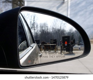 Amish  horse and buggies shown in side view mirror
