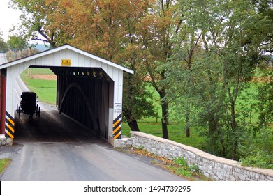 An Amish horse and buggy traverse through a covered bridge in Lancaster County, Pennsylvania