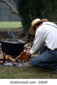 Amish man tending fire