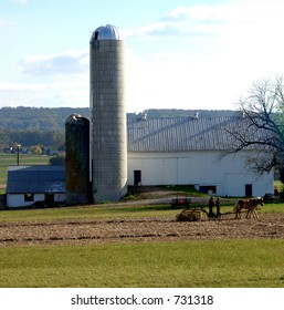 Amish plowing field next to barn