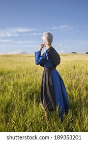 An Amish woman standing in a grassy field in afternoon sunlight
