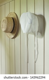 An Amish woman's bonnet and a man's straw hat hanging on a wall
