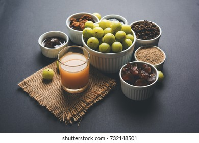 Amla/Indian Gooseberry and it's by products like Chyawanprash, Juice, Digestive Supari or Mouth Freshner, Powder, Sweet Murabba, Pickle. Over moody background. selective focus