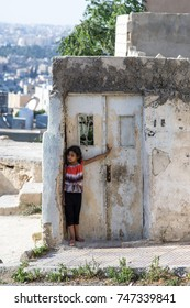 AMMAN, JORDAN - JULY 2016 - A girl peers out onto the street in Amman, the capital of Jordan, during a hot summer day in holy month of Ramadan.