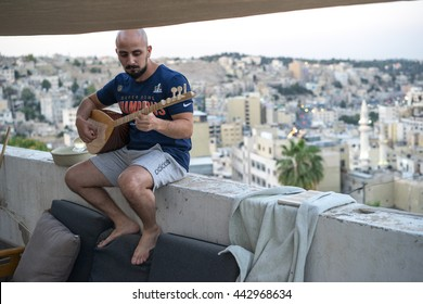 AMMAN, JORDAN - June 10, 2016: A musician plays a saz, a traditional Middle Eastern instrument, on a rooftop in the evening during Ramadan in downtown Amman, Jordan on June 10, 2016.