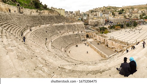 Amman, Jordan, March 2020: View from the top of the Roman Theatre, with tourists visiting and wandering around the roman ruins of Amman