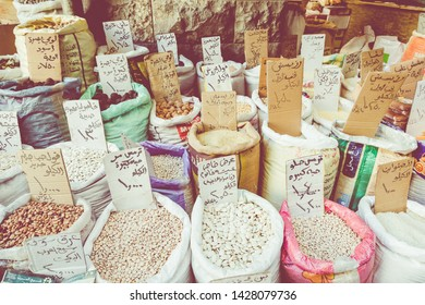 AMMAN, JORDAN - MAY 18, 2019: Spices, nuts and sweets shop on the market in Amman downtown, Jordan. Choice of Arabic spices on the Middle East bazaar, Jordan