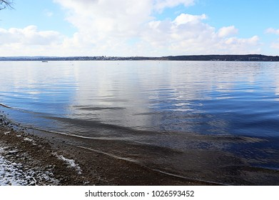 Ammersee Bavarian lake idyllic winter view, shore covered by snow and blue sky reflecting on the calm water surface