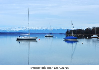 Ammersee Lake, Germany with sailingboats and scenic view on the snow covered alp mountains