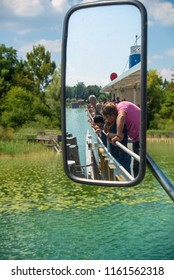 Ammersee,Germany-August 20,2018: Passengers watch from the railings as a sightseeing ship arrives at a pier