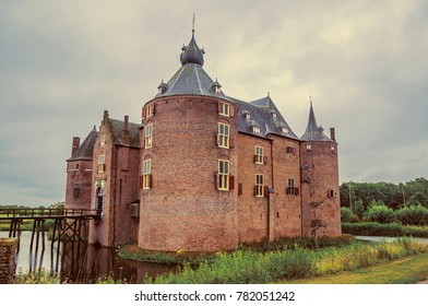 Ammersoyen Castle with its brick towers, wooden bridge, water filled moat and gardens on cloudy day. Near to the historic and vibrant city of s-Hertogenbosch. Southern Netherlands. Retro vintage filte
